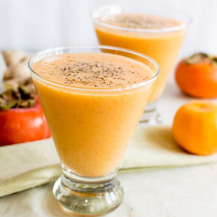 Immune Boosting Persimmon Ginger Smoothie is shown in the serving glasses with all its ingredients as props in this image