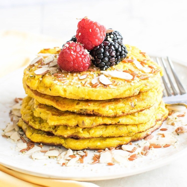 A stack of Anti-Inflammatory Turmeric Pancakes with the fork as a prop is shown in this image