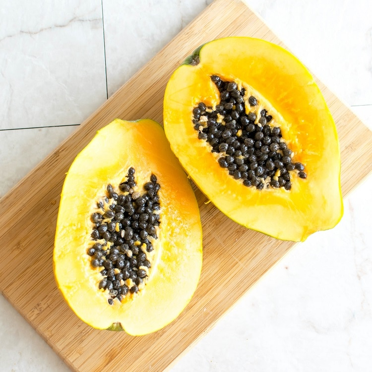 Raw papaya cut into half on a wooden board