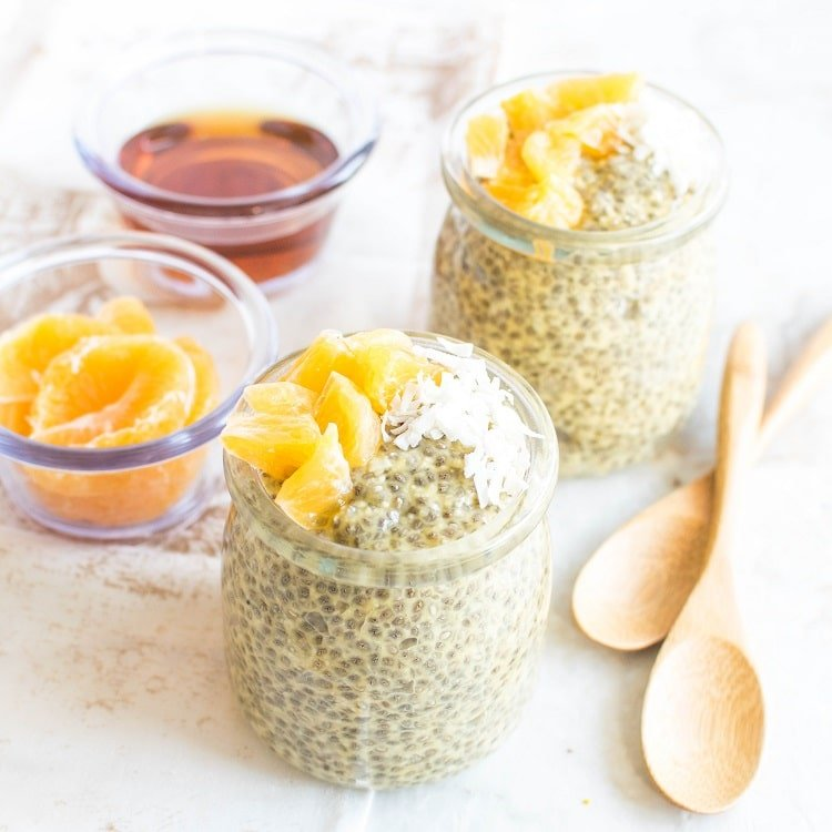 Orange Macaroon Vegan Chia Seed Pudding in serving jars with wooden spoons on the side and fresh oranges as the prop