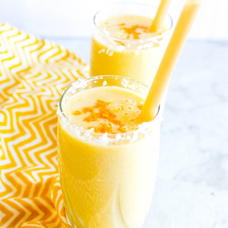 A 45 degree angle of Tropical Coconut Turmeric Smoothie in serving glasses