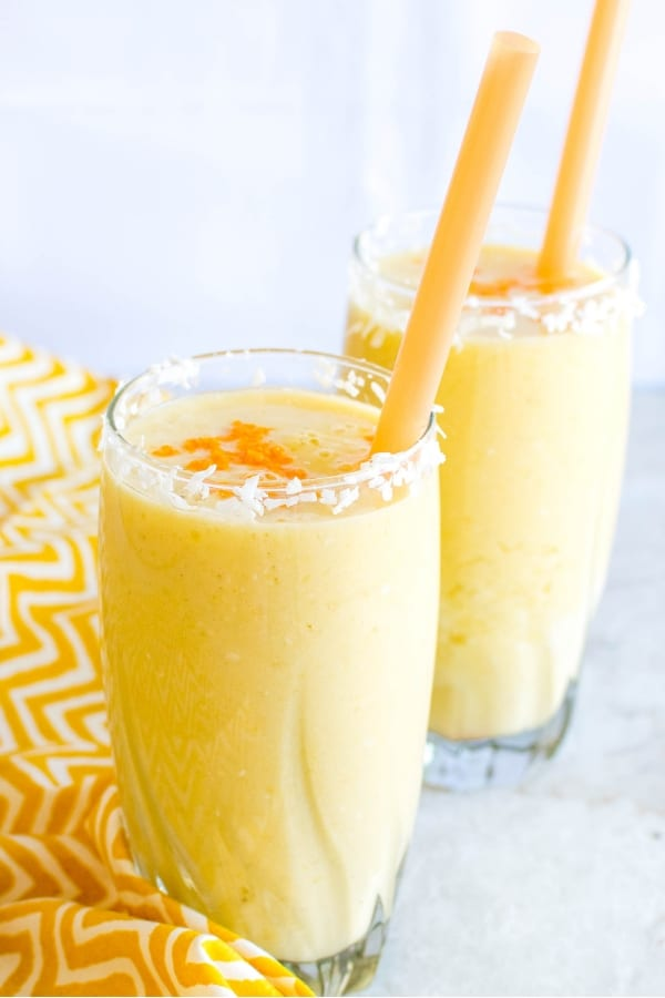 Tropical Coconut Turmeric Smoothie in two tall glasses with straws