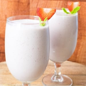 A close front view of vegan Strawberry Chocolate Lassi with fresh mint leaves as a decoration