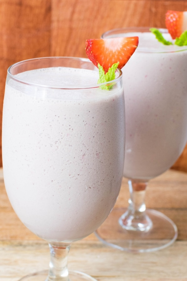 Two tall glasses filled with Vegan Strawberry Chocolate Lassi and garnished