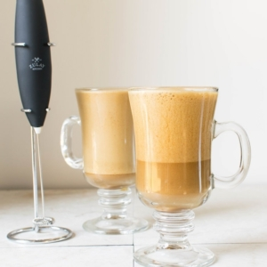 Two tall glasses filled with iced cappuccino and milk frother on the side