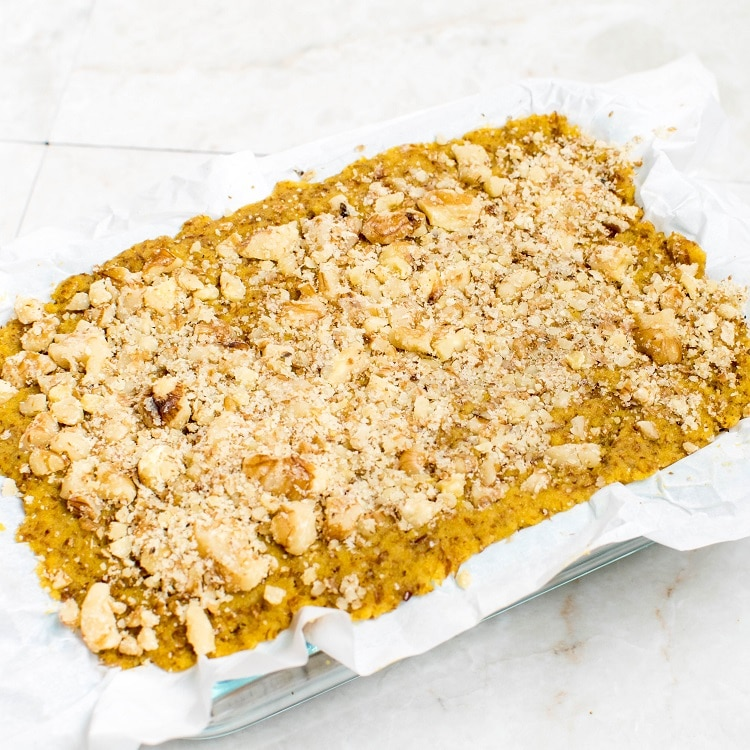 Pumpkin bars dough topped with crushed walnuts and settled in a glass container
