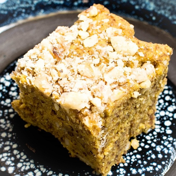 A close up view of a piece of pumpkin bars on a blue plate