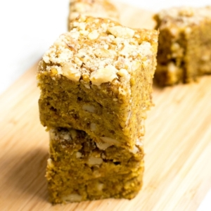 A front view of the stack of No Bake Vegan Pumpkin Bars on a wooden board