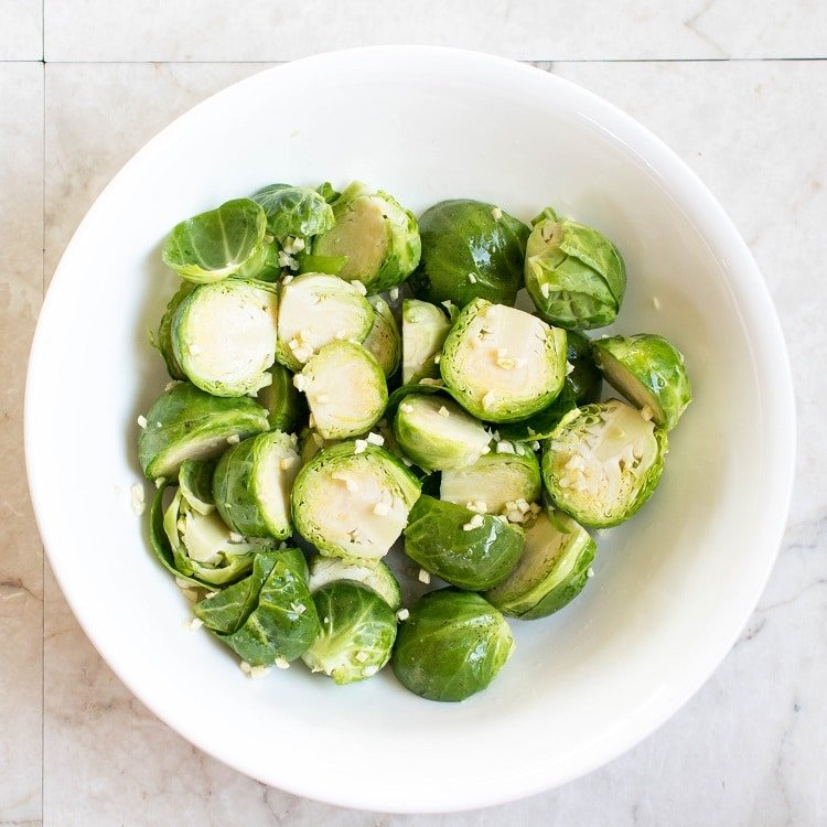Marinated Brussel Sprouts in a white mixing bowl