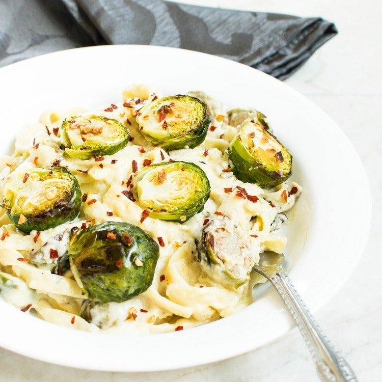 A 45 degree angle view of Roasted Brussel Sprouts Fettuccine Alfredo with a fork as a prop