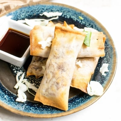 A blue plate stacked with Air Fryer Vegan Spring Rolls with a side of sauce
