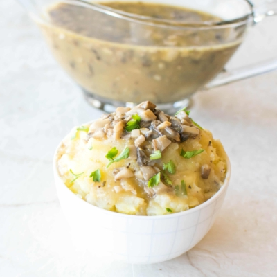 A bowl loaded with mashed potatoes and topped with vegan gravy. A jar filled with vegan gravy at the background.