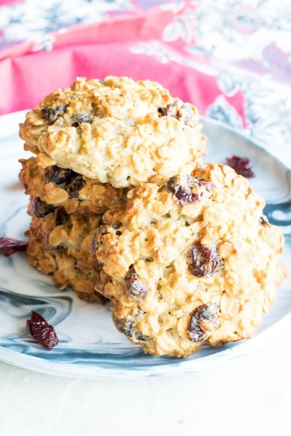 A stack of white chocolate cranberry cookies with a cookie on the focus in a serving plate
