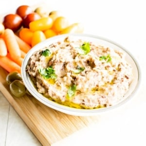 A bowl filled with red bean hummus dip and surrounded by veggies to complement it.