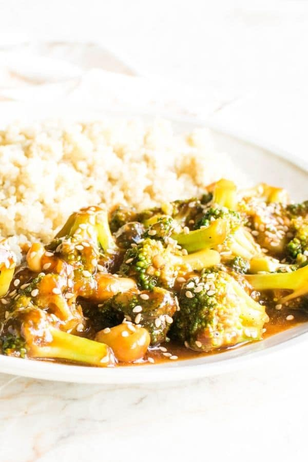 A close up front view of spicy cashew broccoli stir fry along with cooked quinoa on the side