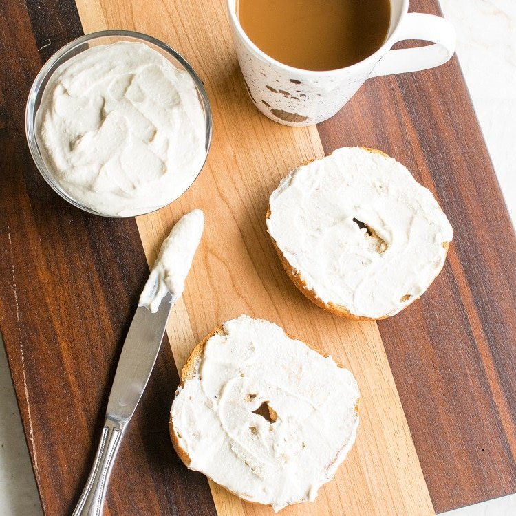 Bagels with Nut Free Vegan Cream Cheese spread on them along with a bowl full of the dip and a cup of coffee on a wooden board