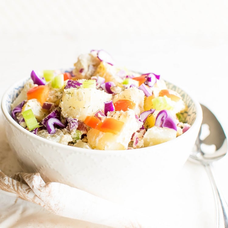 A close up front view of healthy vegan potato salad in a bowl with a large serving spoon as the prop