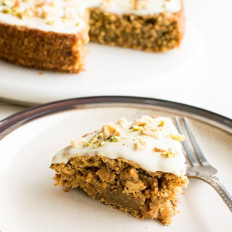 Sliced vegan carrot cake with oat flour with the rest of the cake at the background