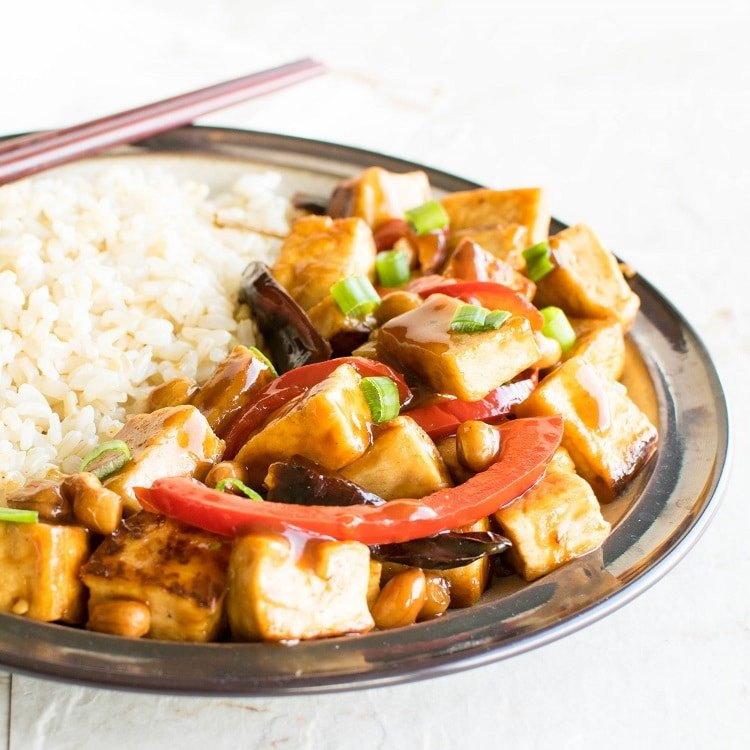 Kung Pao Tofu served with brown rice with chopsticks
