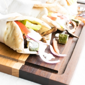 A front view of vegan gyros on a wooden board