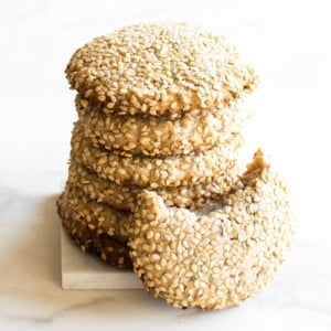 stacked one bowl tahini cookies with an eaten cookie on the side