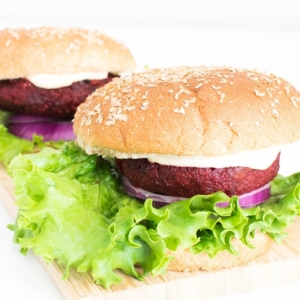 front view of 2 spicy beet burger on a wooden board