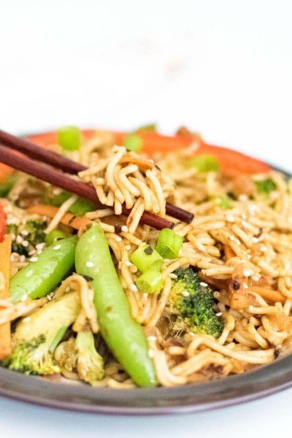 chop sticks picking up almond butter vegetable stir fry noodles from the plate.