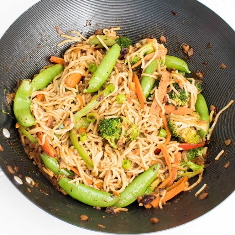 Top view of almond butter vegetable stir fry noodles in a wok