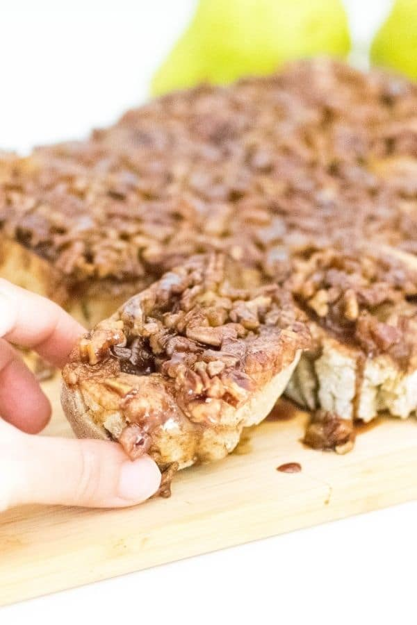pear stuffed pecan sticky buns in  a hand with a focus.