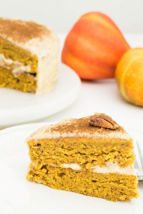 A slice of Pumpkin Cake Recipe with Quinoa Flour  served on a plate with the entire cake in the background.