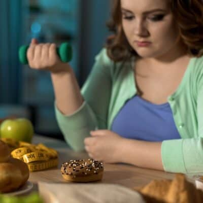 An overweight lady contemplating her dilemma for eating when under stress.