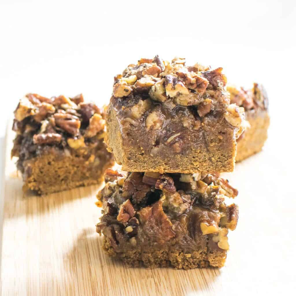A front view of stacked pecan pie bars squares.