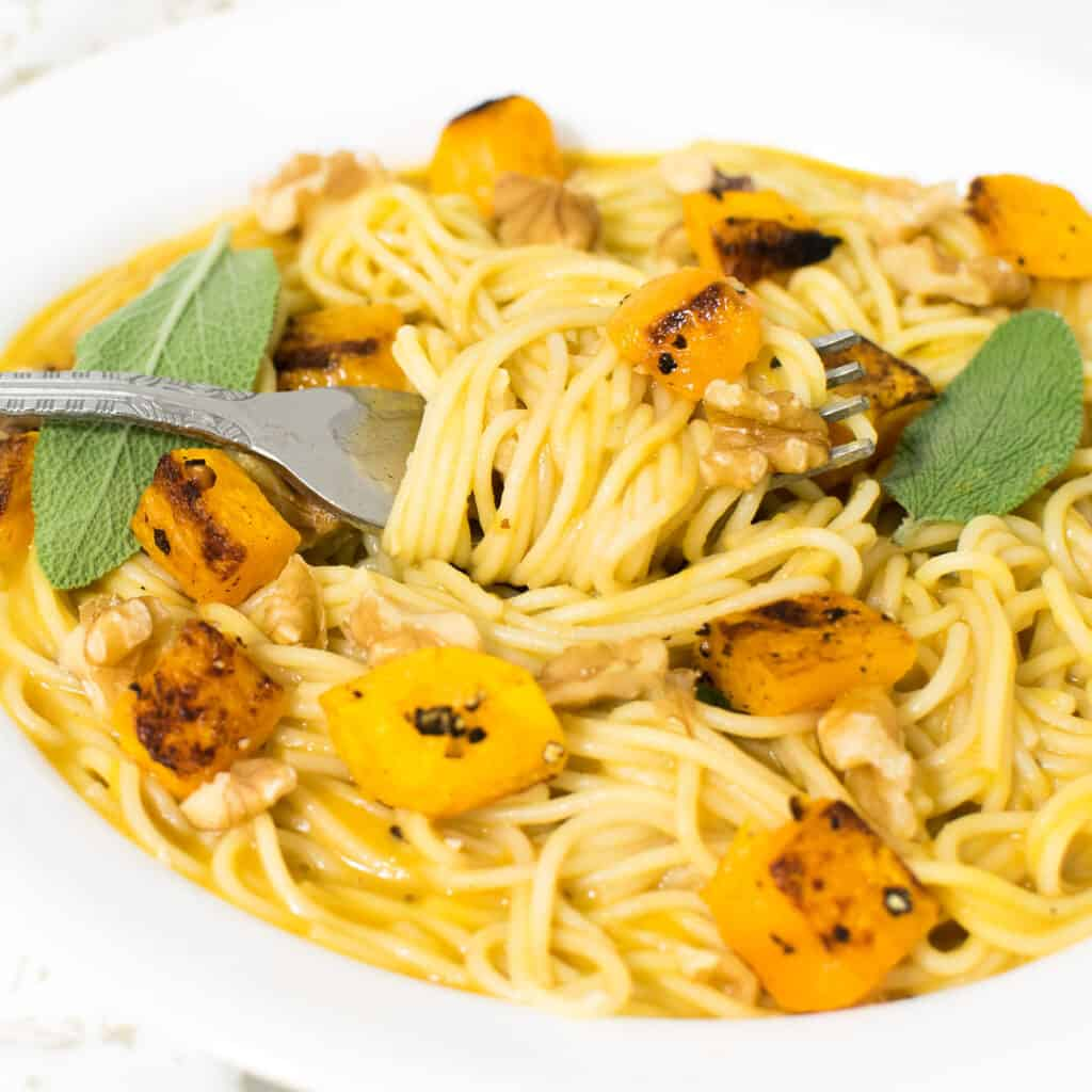a fork with butternut squash pasta with a close up view.