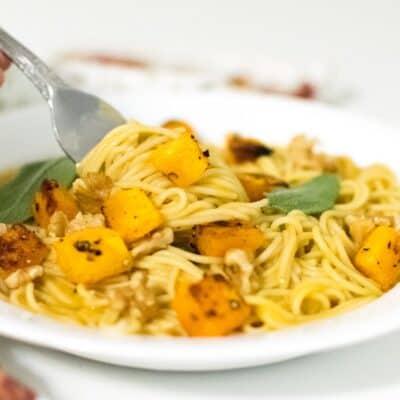 A fork rolling in butternut squash pasta.