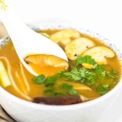 A spoon dipping in instant pot tom yum soup recipe.
