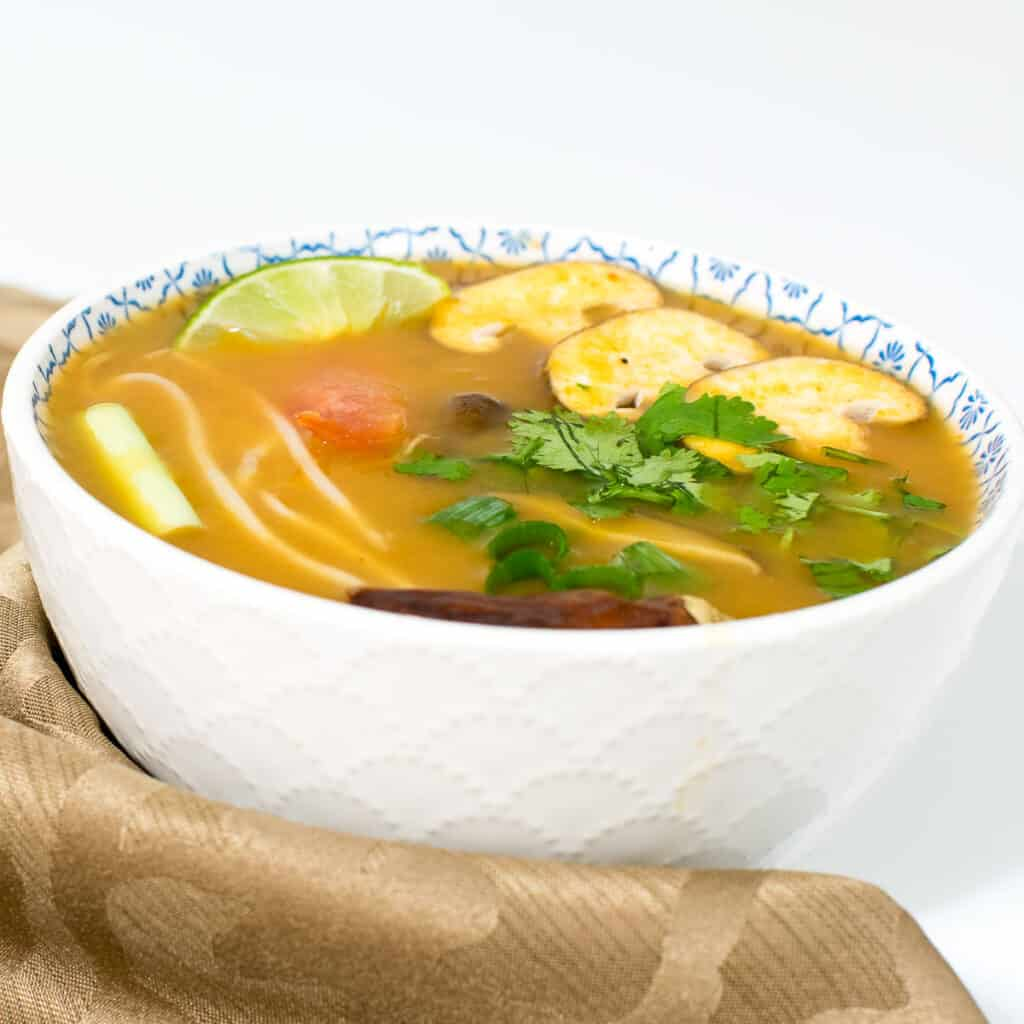 A front view of instant pot tom yum soup recipe in a serving bowl.