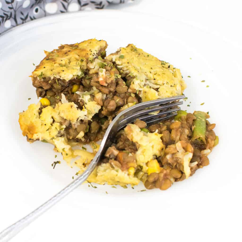 close up view of lentil shepherd's pie on a serving plate with a fork.