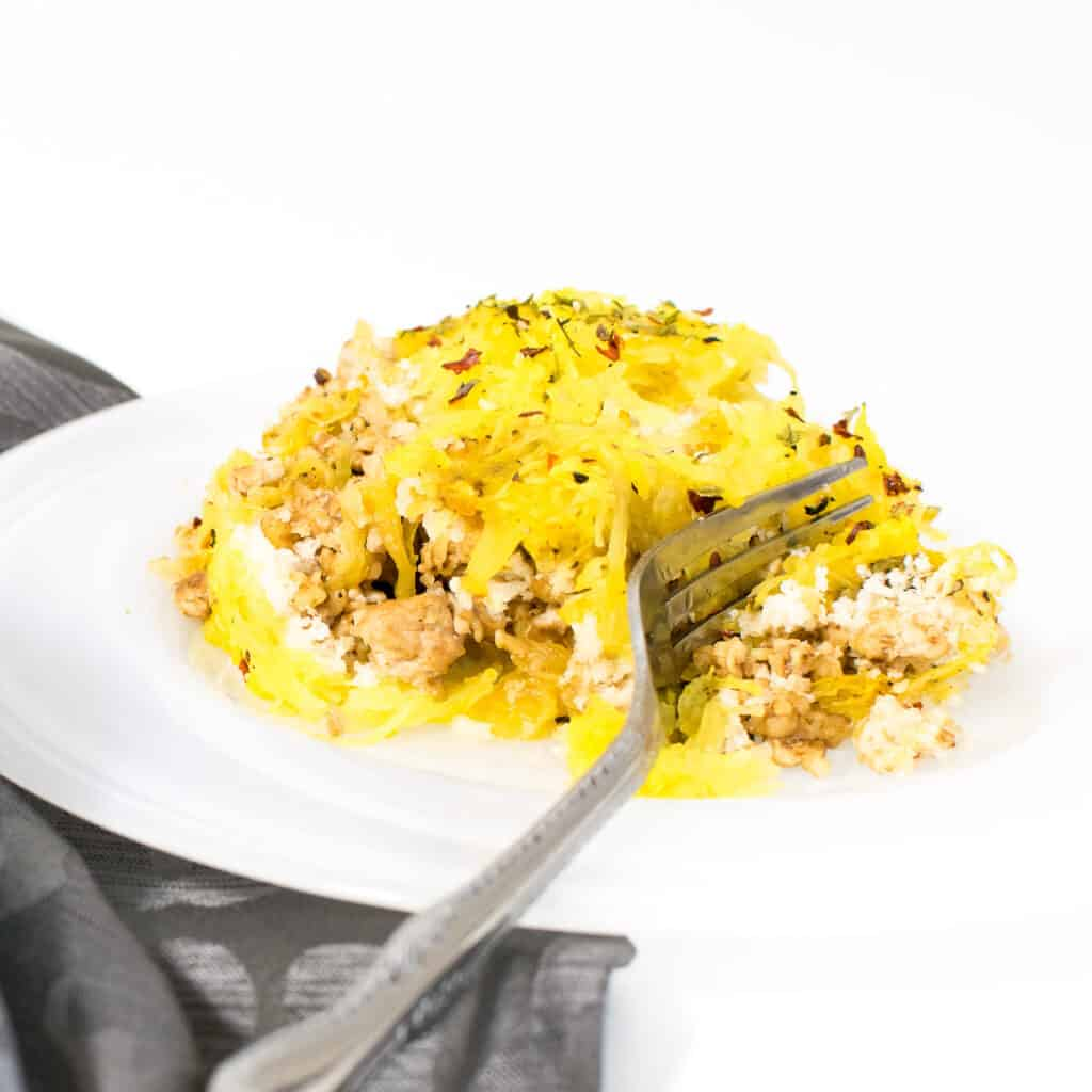 a fork digging into spaghetti squash casserole on a serving plate.