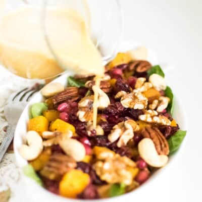 dressing pouring over butternut squash salad