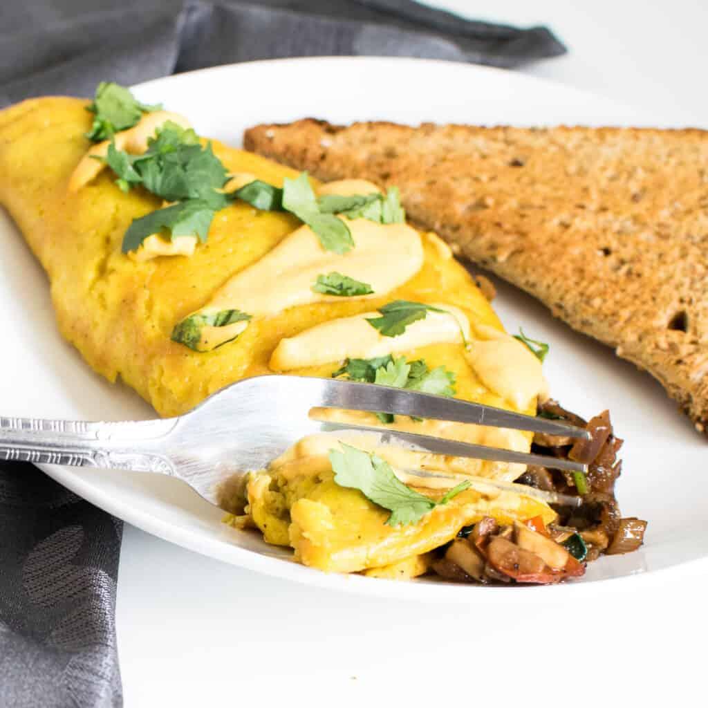 a fork digging through vegan omelette.
