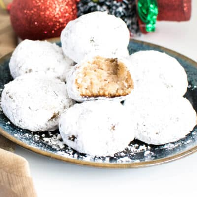 A stack of snowball cookies with half eaten cookie at the top.
