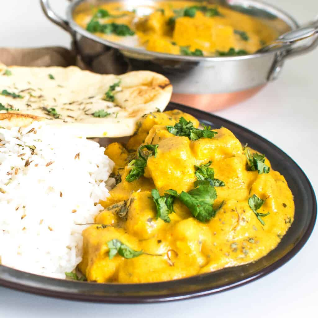 A front view of butter tofu served with rice and naan.