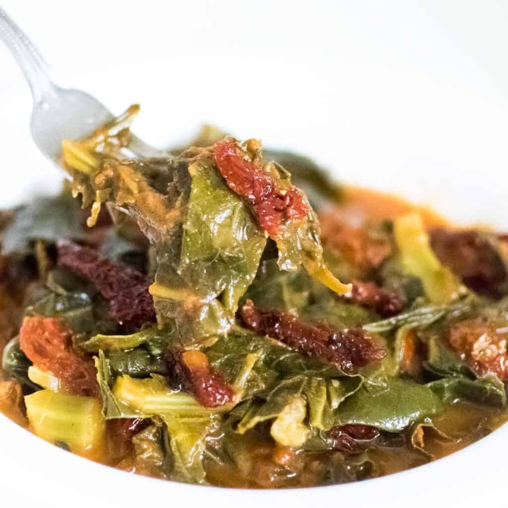 a fork scooping out vegan collard greens
