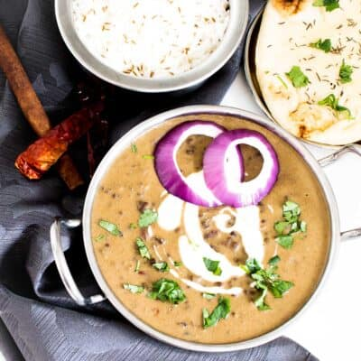 top view of dal makhani in kadai with rice and naan