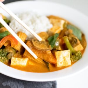 chop sticks pricking up Thai red curry vegetables from a plate.