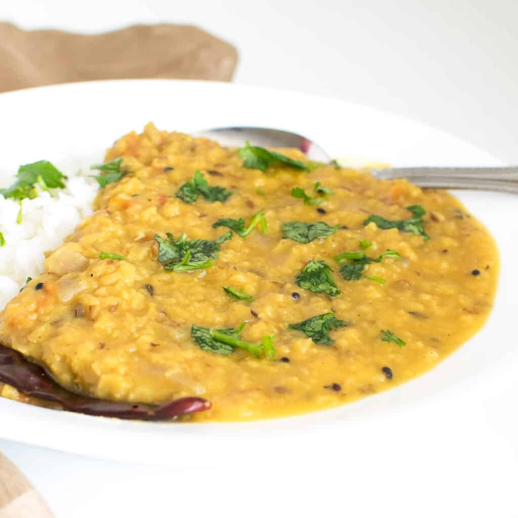a front view of served red lentil dal.