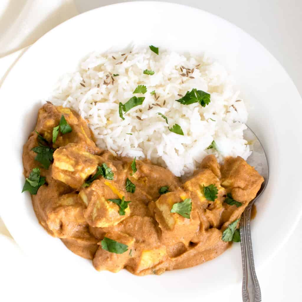 top view of tofu tikka masala served with rice.