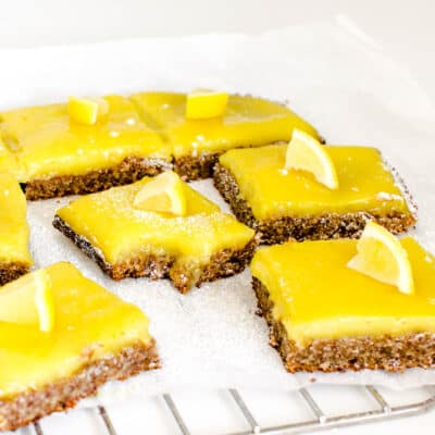 a front view of vegan lemon bars on a parchment paper with a half eaten slice in the middle.