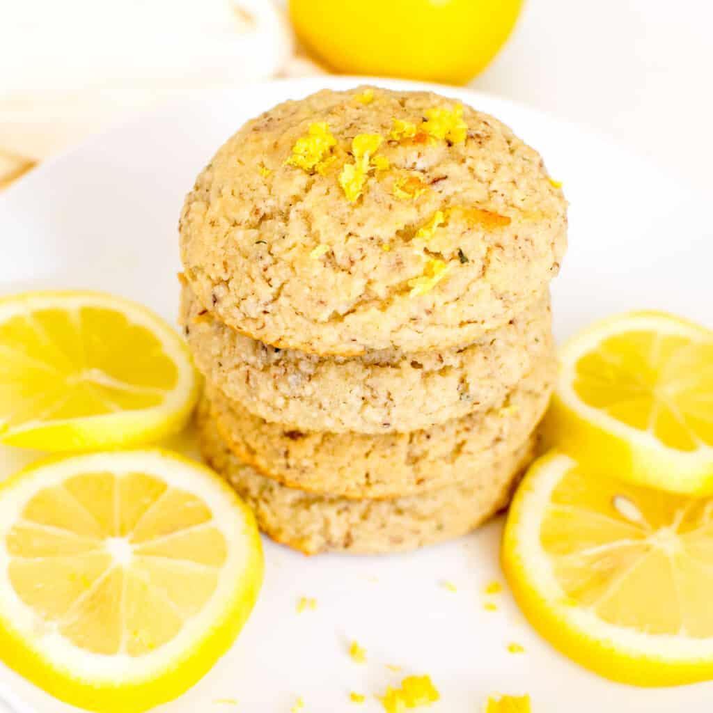 a 45 degree angle view of stacked vegan lemon cookies.