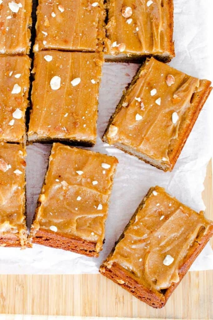 top view of scattered peanut butter cake slices on a wooden board.